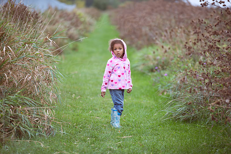 Portrait of a young girl walking down a green grassy lane and looking back curiously by anya brewley schultheiss for Stocksy United