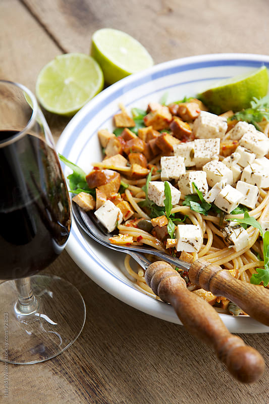 Spaghetti with vegan sausages, arugula and vegan feta by Harald Walker for Stocksy United