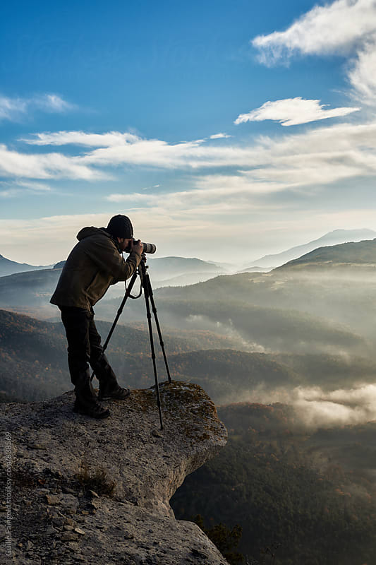 Professional photographer taking photo while standing on cliff against of beautiful landscape by Guille Faingold for Stocksy United