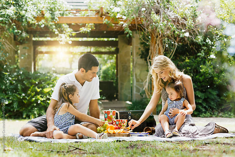 Young couple having a picnic with their two daughters by Image Supply Co for Stocksy United