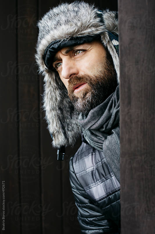 Portrait of a man looking away wearing a winter furry hat by Beatrix Boros for Stocksy United