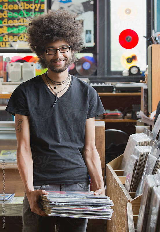 Portrait of young man holding records in record shop by Andersen Ross Photography for Stocksy United