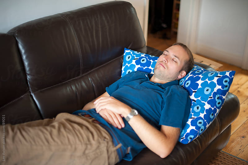 man relaxing on a sofa by Lee Avison for Stocksy United