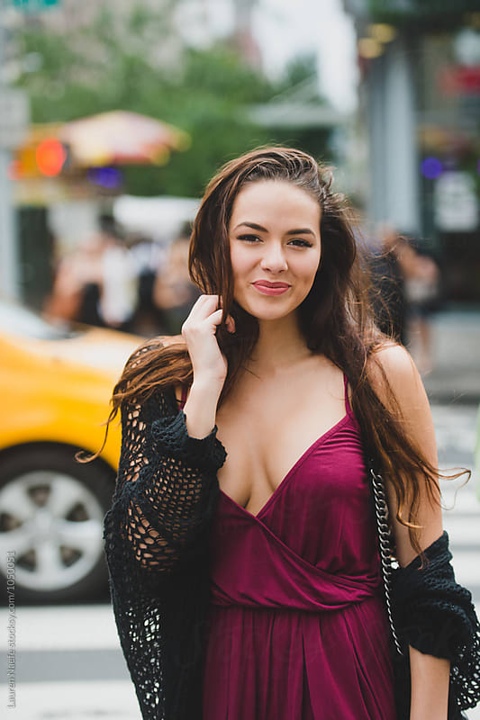 Happy young woman in the city by Lauren Naefe for Stocksy United
