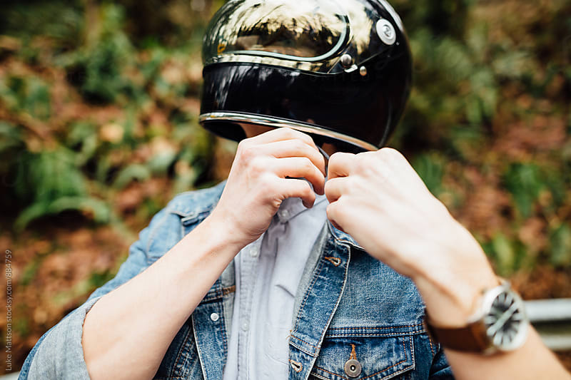 Café Racer Rider Putting On Helmet  by Luke Mattson for Stocksy United