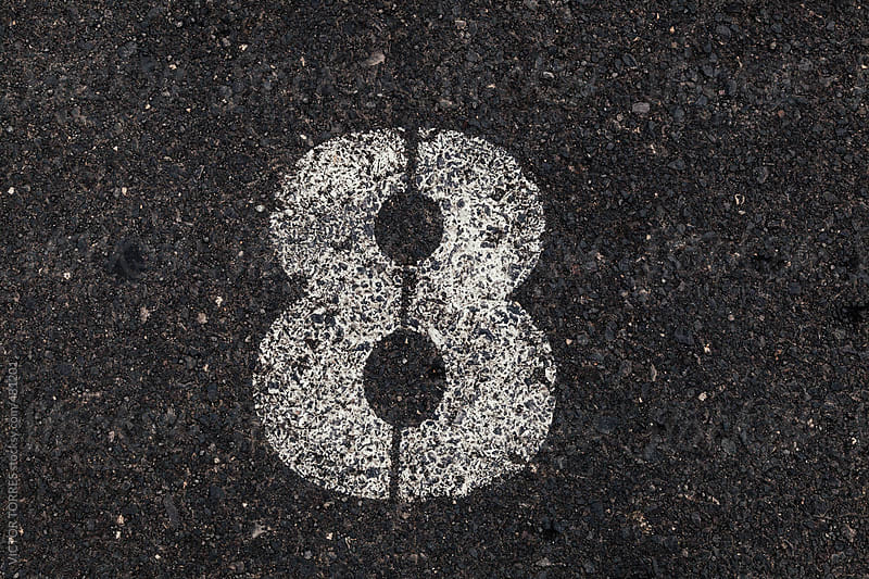 Number 8 Printed on White Over Dirty Asphalt by VICTOR TORRES for Stocksy United