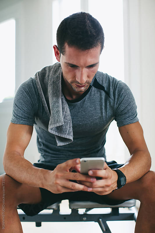 Man using his phone resting after workout at home. by BONNINSTUDIO for Stocksy United