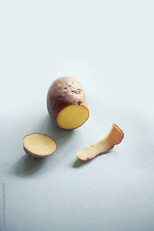 Cut red potatoe and its peel by Laura Stolfi for Stocksy United