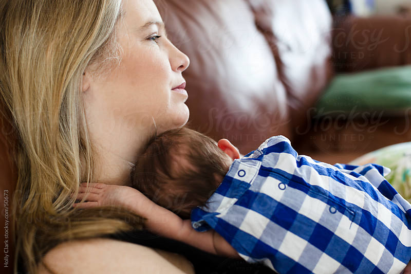 A mother holding her sleeping, newborn daughter in her arms. by Holly Clark for Stocksy United