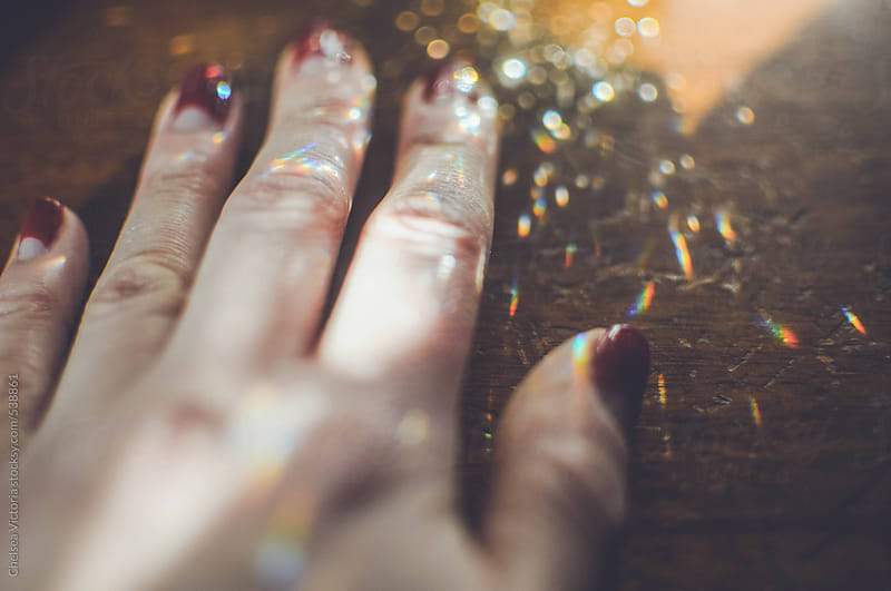 A hand resting on a surface with scattered light by Chelsea Victoria for Stocksy United