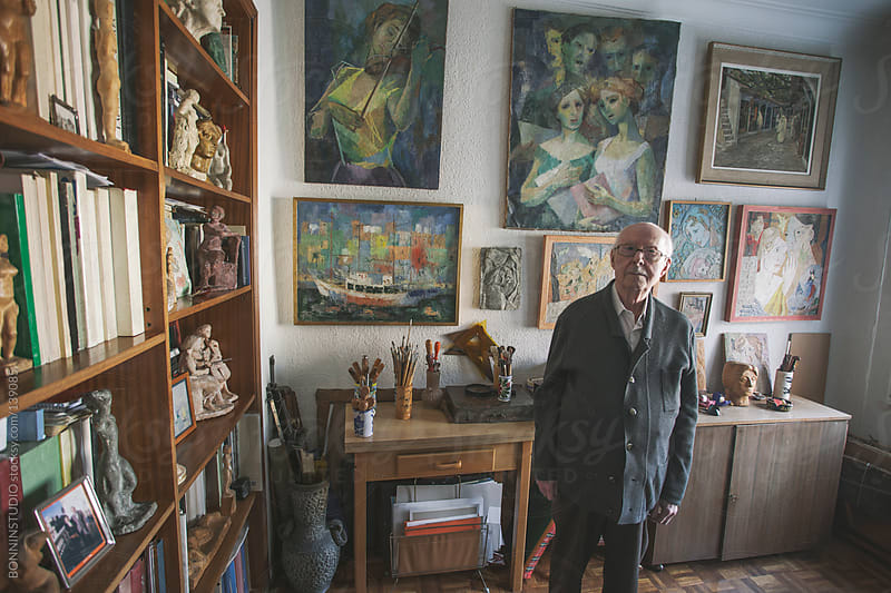 Portrait of a old man standing on his studio of painting and sculpture. by BONNINSTUDIO for Stocksy United