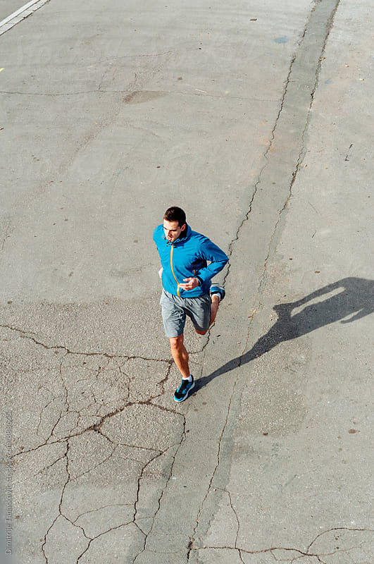 Young man running in the city by Dimitrije Tanaskovic for Stocksy United