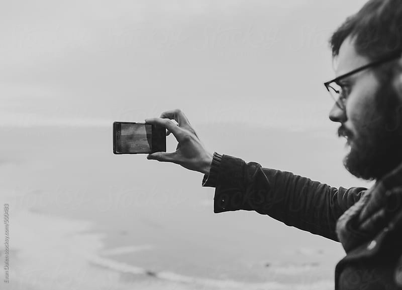 Man taking a photograph with a mobile phone by Evan Dalen for Stocksy United