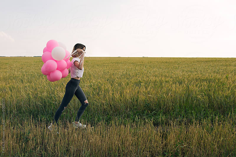 Girl with balloons running along field by Danil Nevsky for Stocksy United