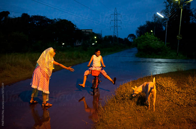 Teenagers making fun and cycling in blue hour by PARTHA PAL for Stocksy United