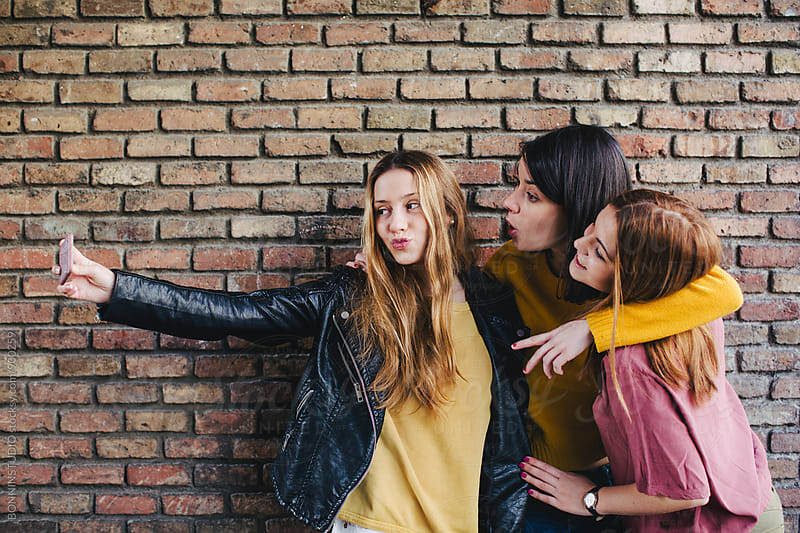 Teen girls taking a selfie with their smartphone. by BONNINSTUDIO for Stocksy United