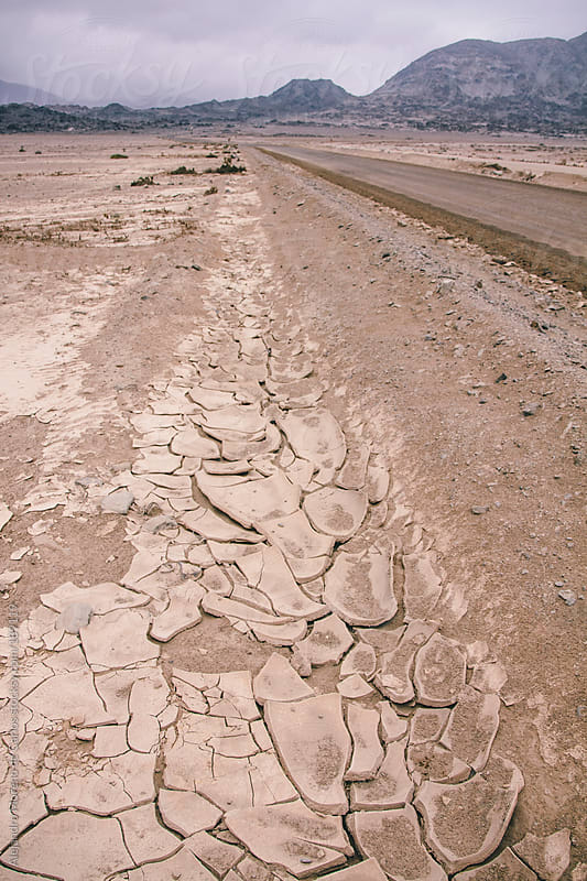 Road on the desert with cracked ground due to drought by Alejandro Moreno de Carlos for Stocksy United