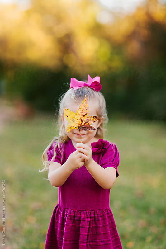 Little girl covering her eyes with an Autumn leaf by Kristen Curette Hines for Stocksy United