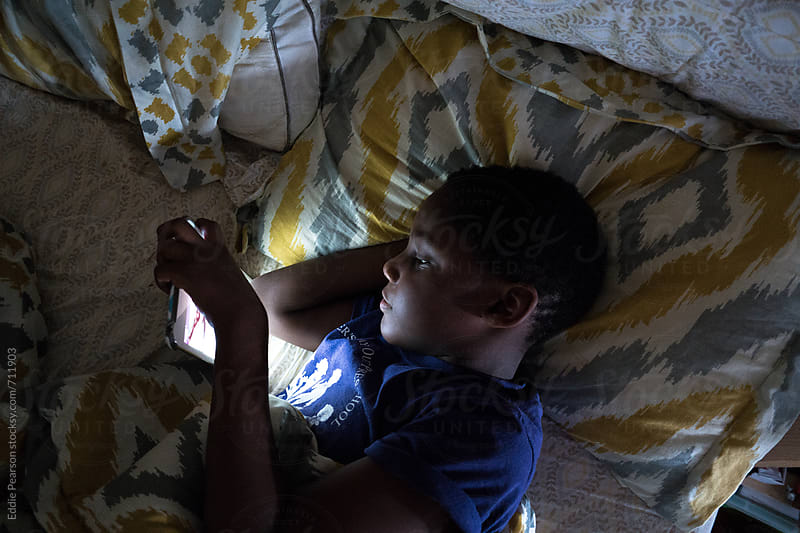 Young boy reading on a tablet by Eddie Pearson for Stocksy United