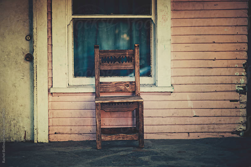 Old carved chair on the porch of a shabby pink house by Rachel Bellinsky for Stocksy United