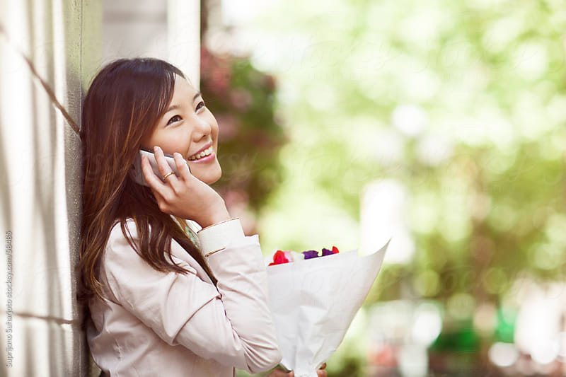Beautiful Asian woman talking on the phone by Suprijono Suharjoto for Stocksy United