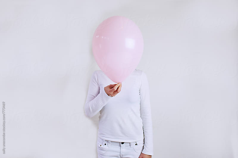 Young woman holding a pink balloon in front of her face by sally anscombe for Stocksy United