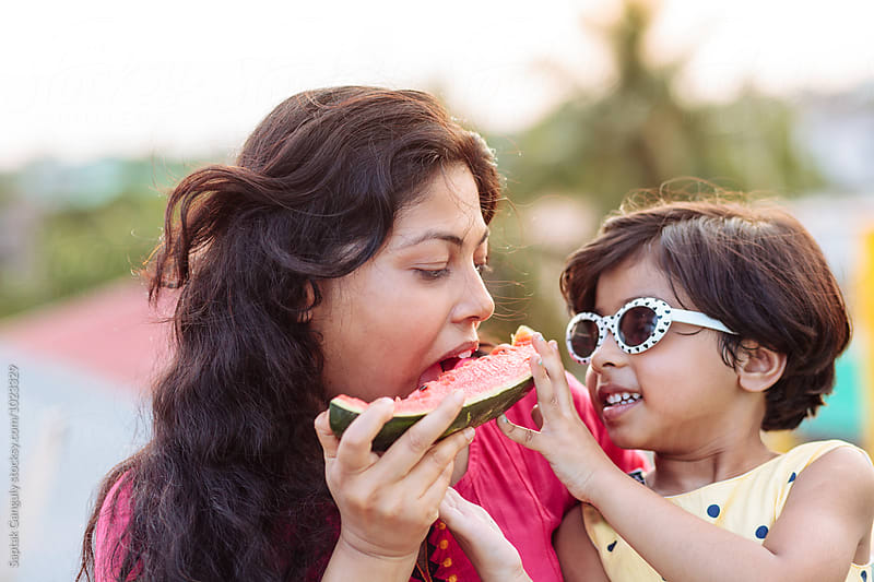 Little girl feeding her mother with watermelon outdoor by Saptak Ganguly for Stocksy United