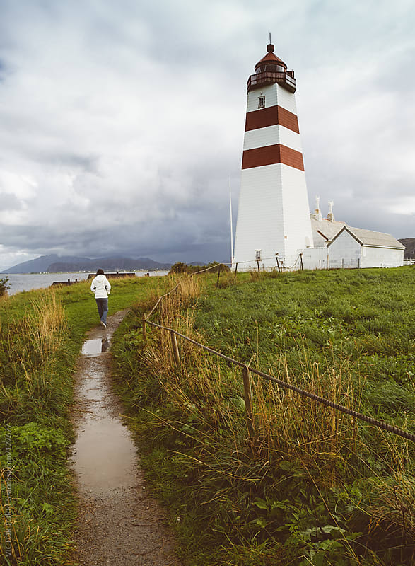Person Walking Through a Wet Foothpath besides Alnes Lighthouse by VICTOR TORRES for Stocksy United