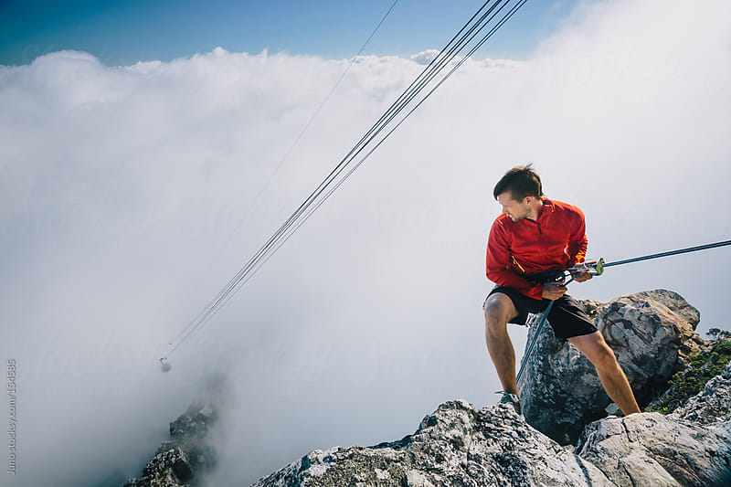 Mountaineer abseilling off the edge of Table Mountain, cable car in the distance by Micky Wiswedel for Stocksy United