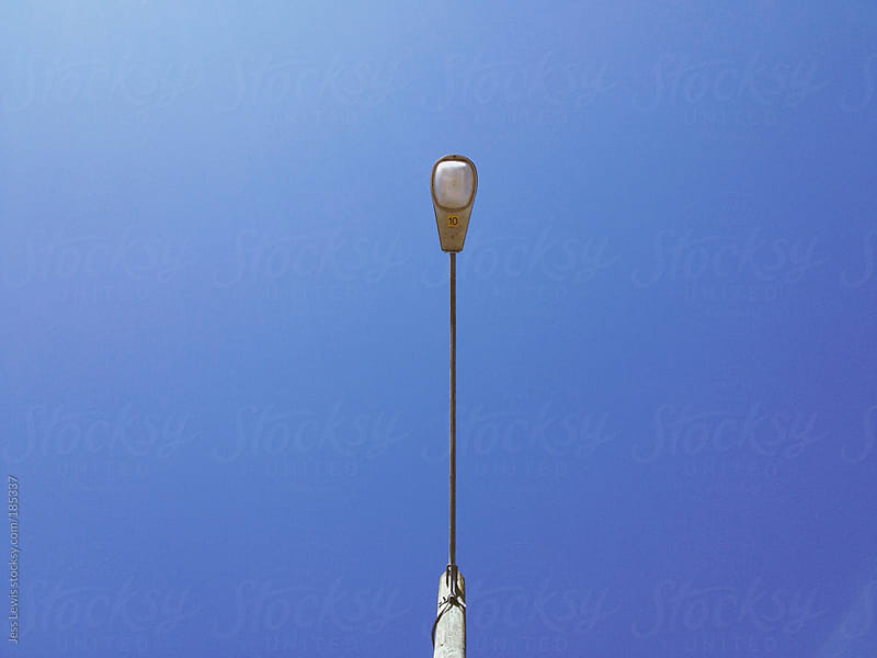street lamp against blue sky by Jess Lewis for Stocksy United