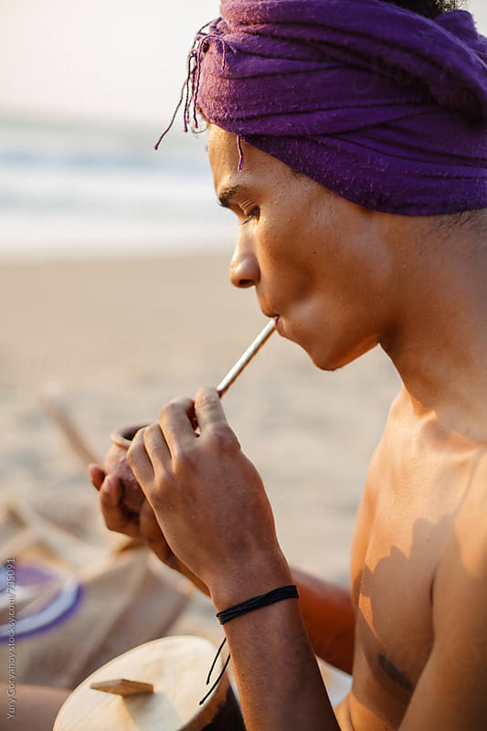 Portrait of a young man on the beach drinking mate by Yury Goryanoy for Stocksy United