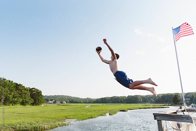 Teen Jumping off Dock to Catch a Football by Raymond Forbes LLC for Stocksy United