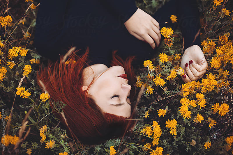 Girl laying in a meadow of flowers by Ani Dimi for Stocksy United
