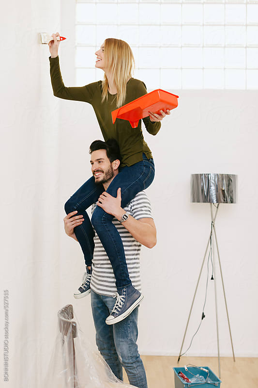 Young woman giving his girlfriend a piggyback so she can paint the wall. by BONNINSTUDIO for Stocksy United