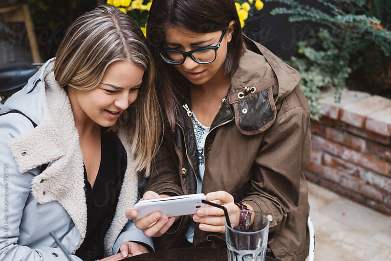Two Female Friends Using Phone While Having Coffee by Katarina Radovic for Stocksy United