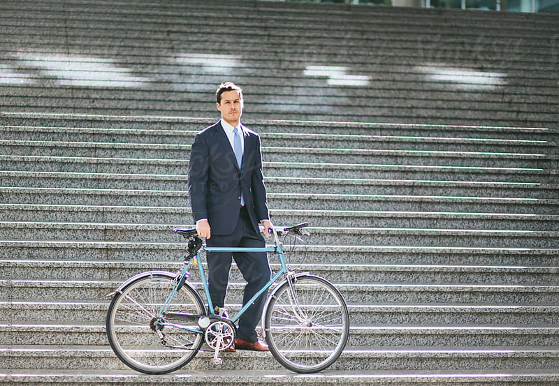 Serious young business man in suit standing with his bike on a s by Ivo de Bruijn for Stocksy United