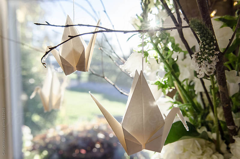 Japanese paper cranes hanging from a floral centerpiece by Cara Dolan for Stocksy United