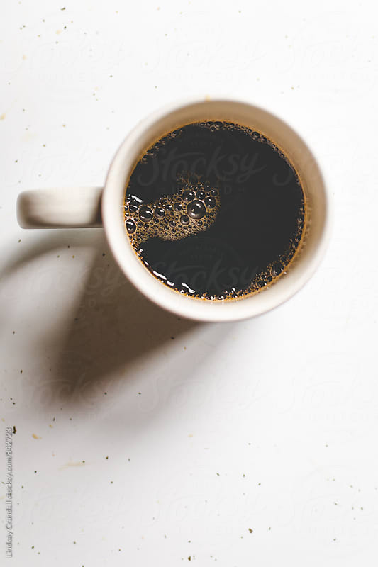 Black coffee in mug with bubbles by Lindsay Crandall for Stocksy United