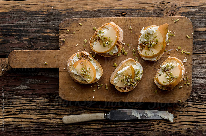 Crostini with Goat Cheese and  Pear on Wood Cutting Board by Jeff Wasserman for Stocksy United