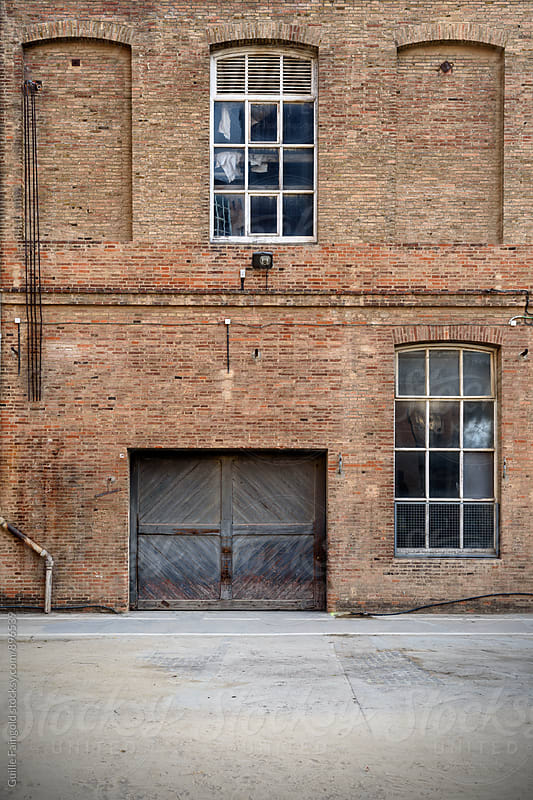 Frontal view of factory facade, old brick wall with windows and wooden door by Guille Faingold for Stocksy United