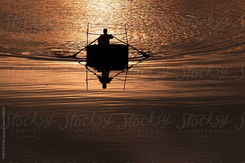 Person with floating vessel in a lake at evening time by PARTHA PAL for Stocksy United