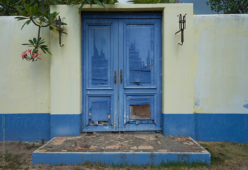 Blue rustic door over eroded building facade in Venezuela. by Gabriel Diaz for Stocksy United