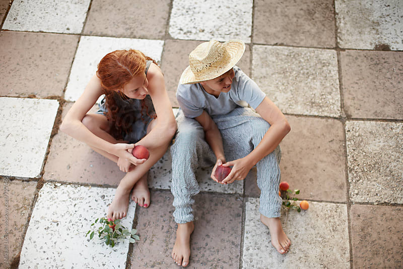 Young couple of adolescents sitting on the ground and eating some fruit by Miquel Llonch for Stocksy United