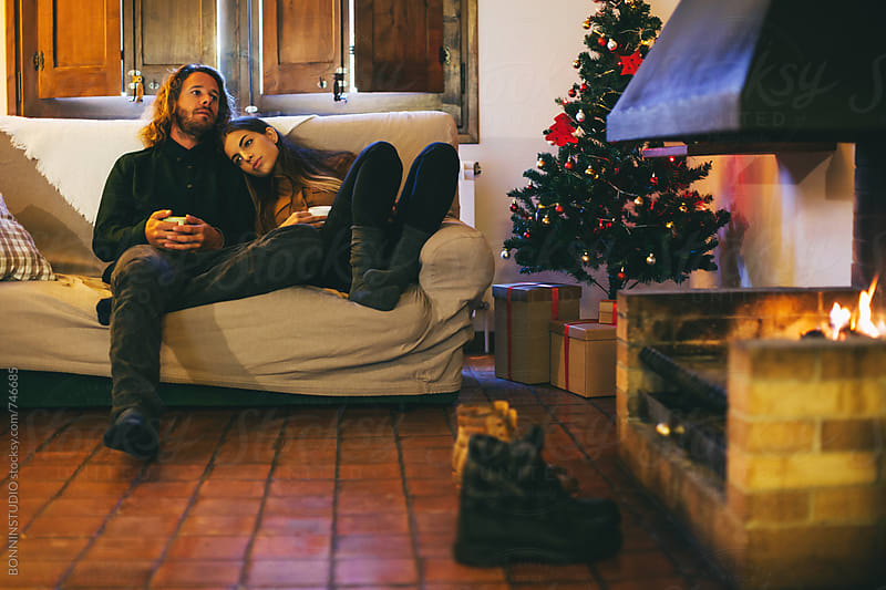 Couple resting by the fireplace on Christmastime. by BONNINSTUDIO for Stocksy United