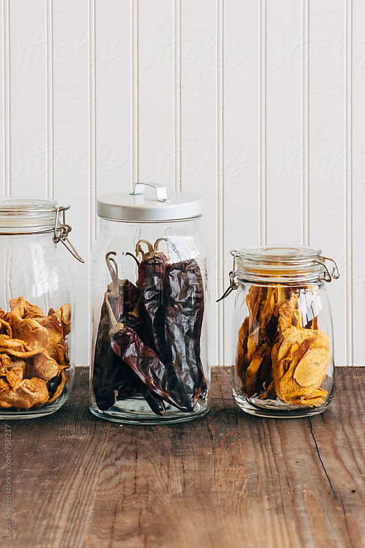 Three jars with dried mango, peppers, apples on a wood counter. by Lucas Saugen for Stocksy United