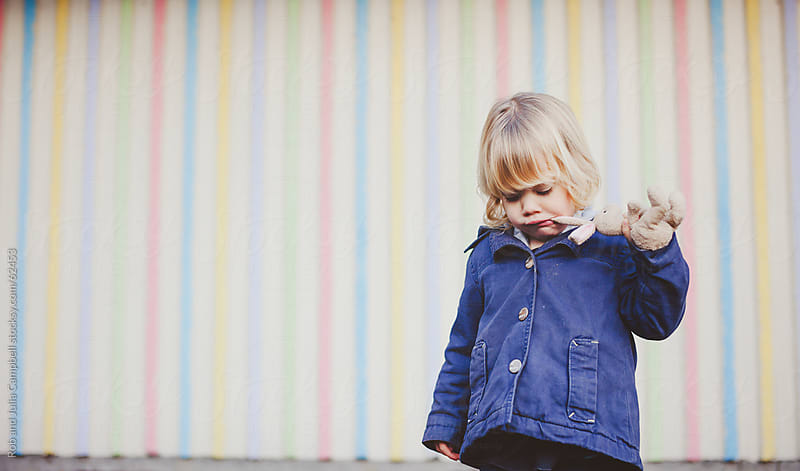 Cute, young girl pouting in front of coloured wall by Rob and Julia Campbell for Stocksy United