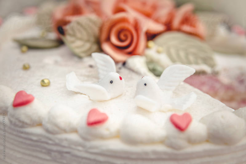 Food: Detail of a wedding cake, two birds by Ina Peters for Stocksy United