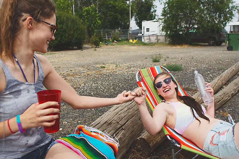 teenage friends pinky swear while sun bathing outside by Tana Teel for Stocksy United