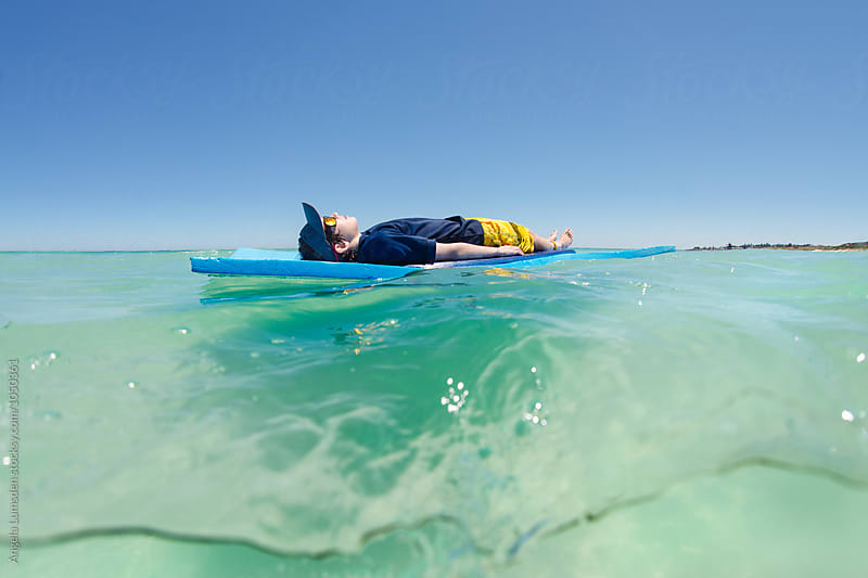 Over under image of a boy floating and relaxing on a large foam mat at the beach in summer by Angela Lumsden for Stocksy United