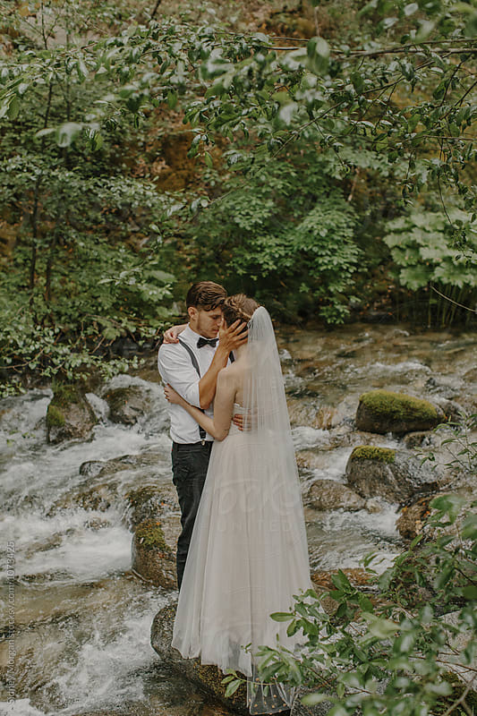 Wedding Couple in Creek by Sidney Morgan for Stocksy United